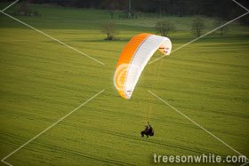 Tandem Paragliding over green fields.